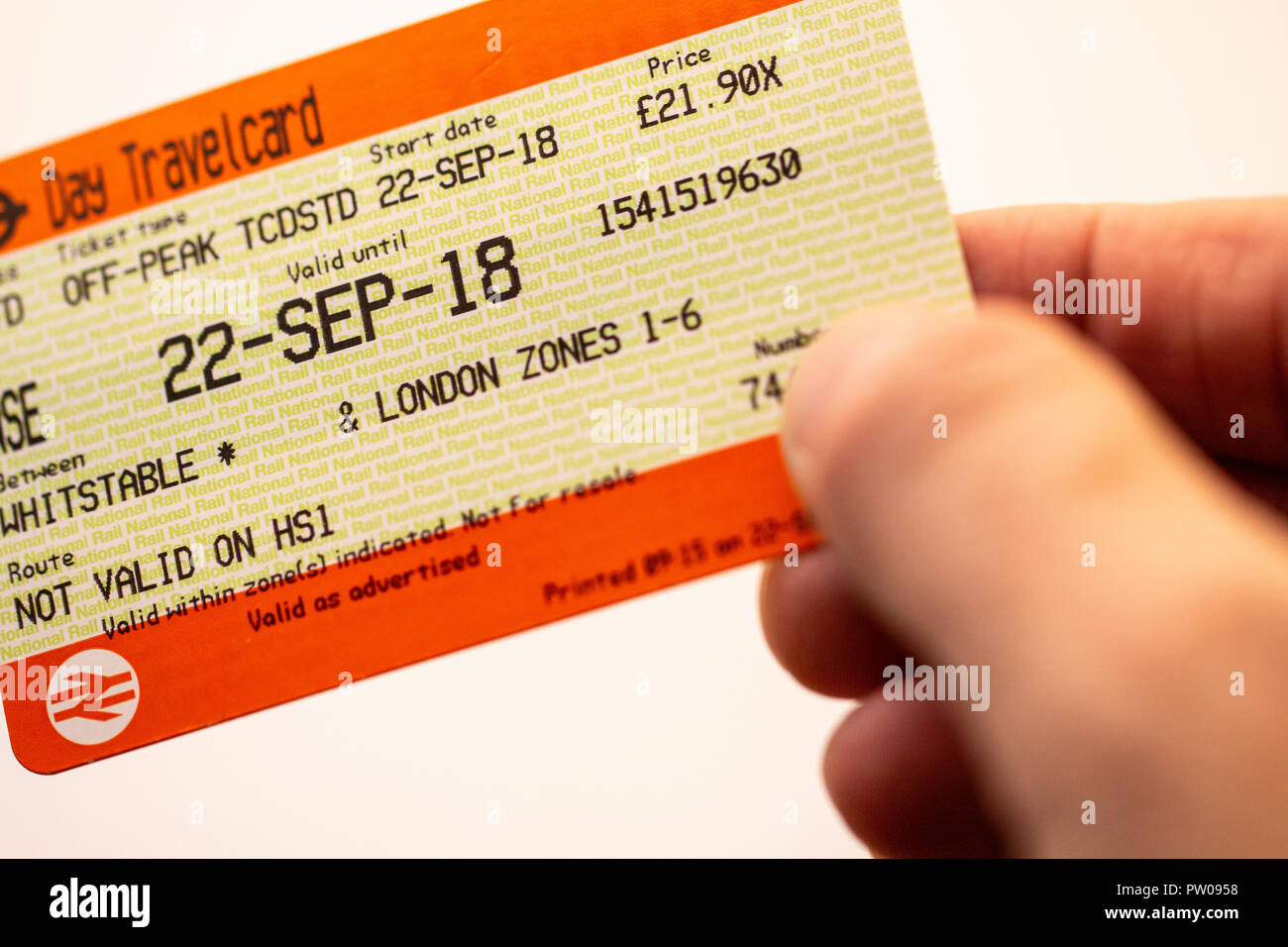 Hand holding British railway ticket, standard off peak one day travelcard, whitestable to London zones 1-6. White plain background. - Stock Image