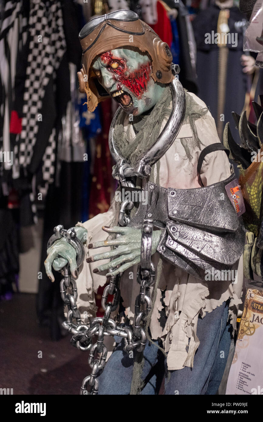 A mannequin decorated with a frightening mask, rubber helmet and giant handcuffs at a costume store in Manhattan, New York City. - Stock Image