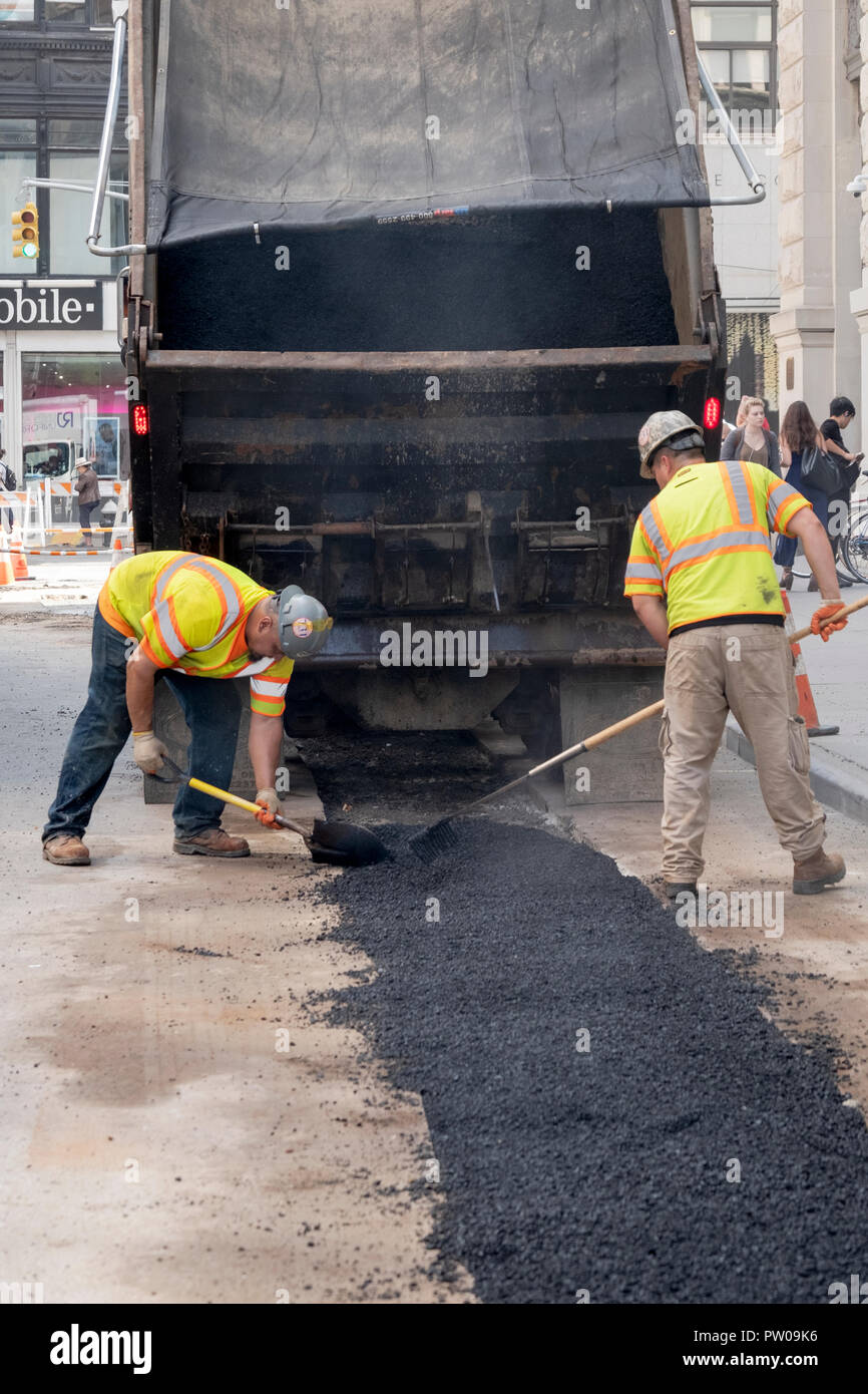 Two construction workers repave a road that had been opened to repair steam pipes, On Waverly Place in Greenwich Village, New York City. - Stock Image