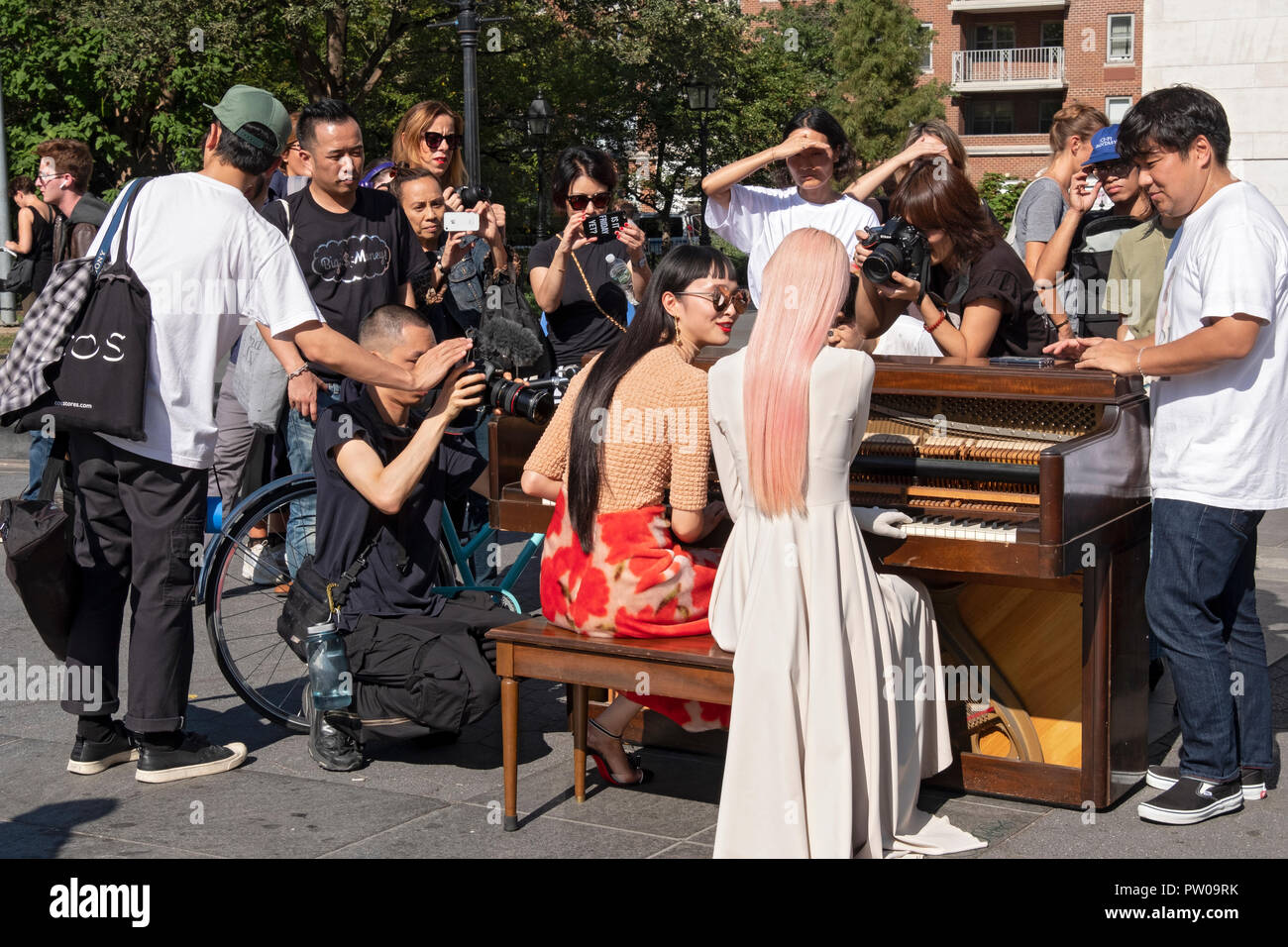 Two beautiful slender Japanese models, their photographers, entourage & onlookers in Washington Square Park in Greenwich Village, New York City. - Stock Image