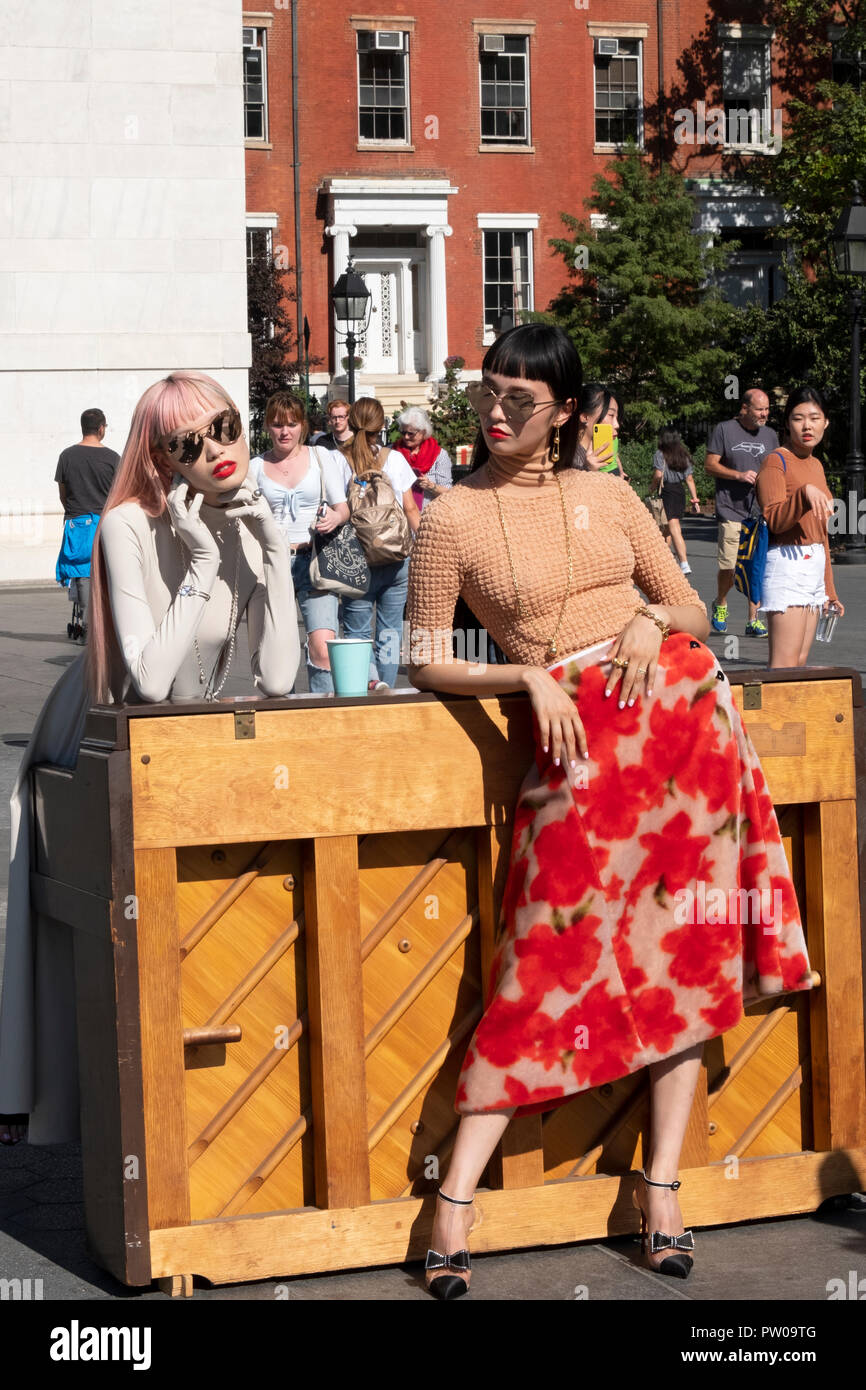 Two beautiful slender Japanese models & onlookers in Washington Square Park in Greenwich Village, New York City on a photo shoot. - Stock Image