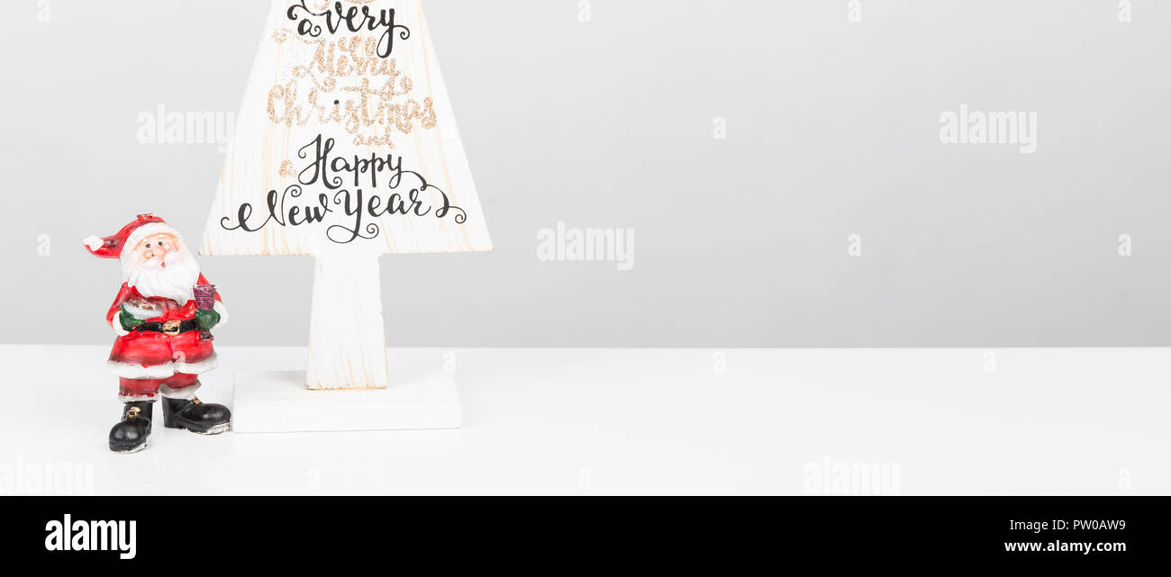 beautiful minimal christmas wood white tree with merry christmass and happy new year written with small santa claus on white backgound banner panor
