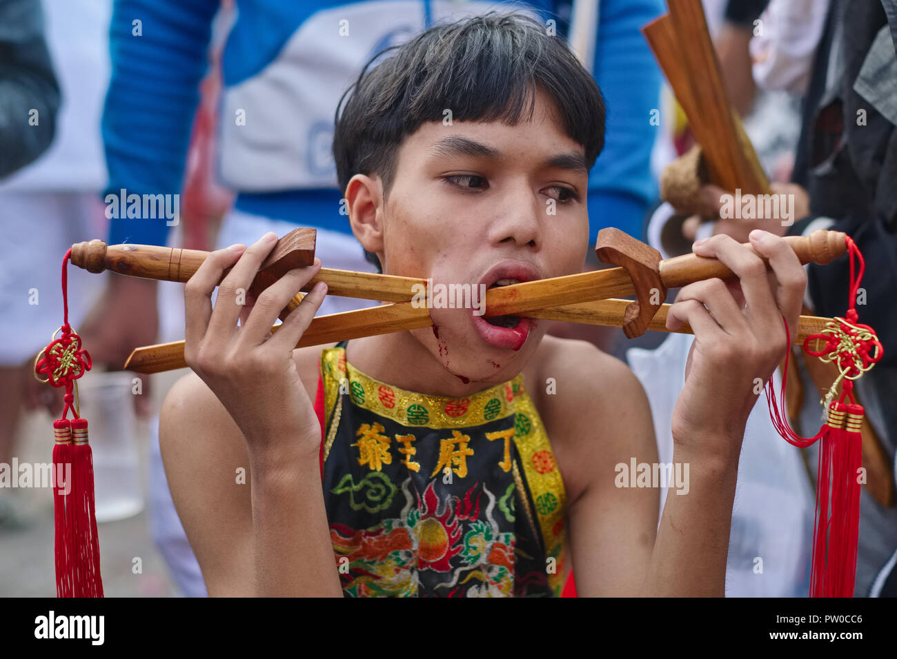 Young participant in the annual, 9 day long Vegetarian Festival in Phuket, Thailand, with cheeks sliced open to insert wooden swords - Stock Image