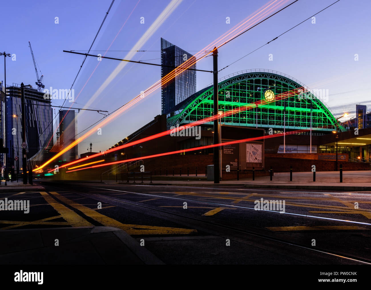 Twilight view of the Manchester Central Convention Centre with a passing tram. The Beetham Tower is in the background. - Stock Image