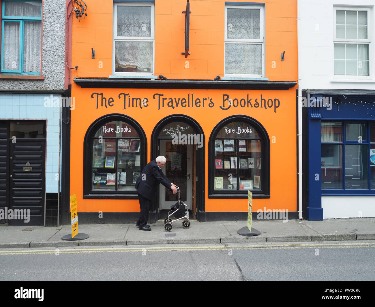 An old man deep in thought on his zimmer frame walks slowly past the Time Traveller bookshop in a little town on the west coast of Ireland. If only. - Stock Image