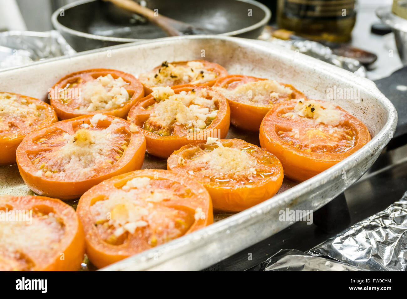 Delicious baked tomatoes with melted cheese on top in oven pan Stock Photo