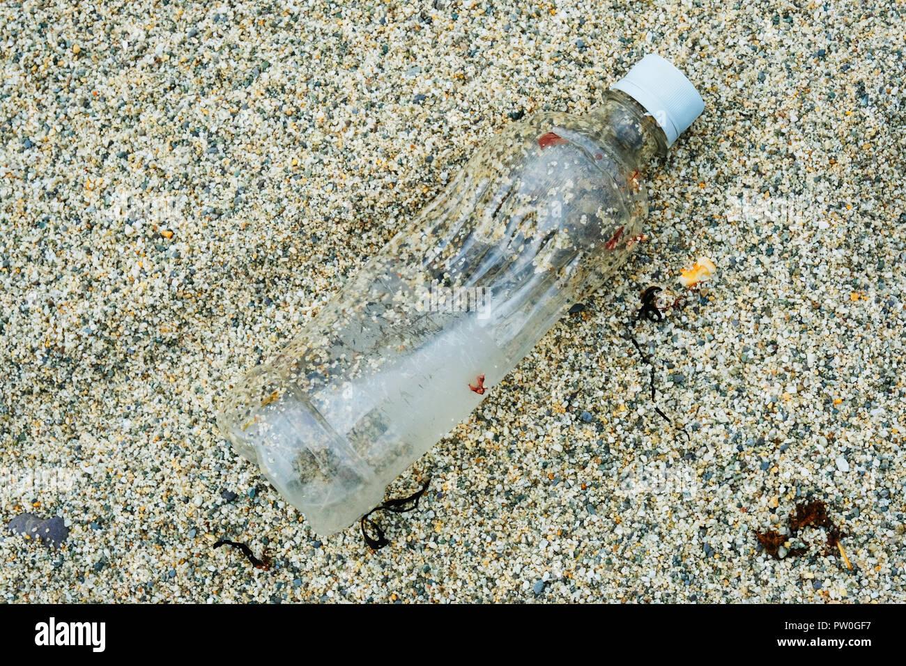 Single plastic bottle left on a sandy beach - John Gollop - Stock Image