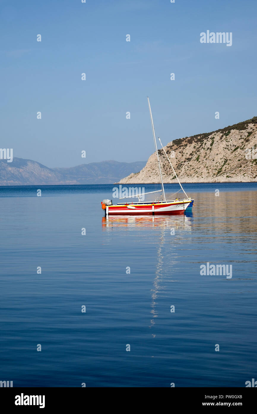 Boats moored in the tranquil bay of Perdhika on the Argo-Saronic island of Aegina, Greece. - Stock Image