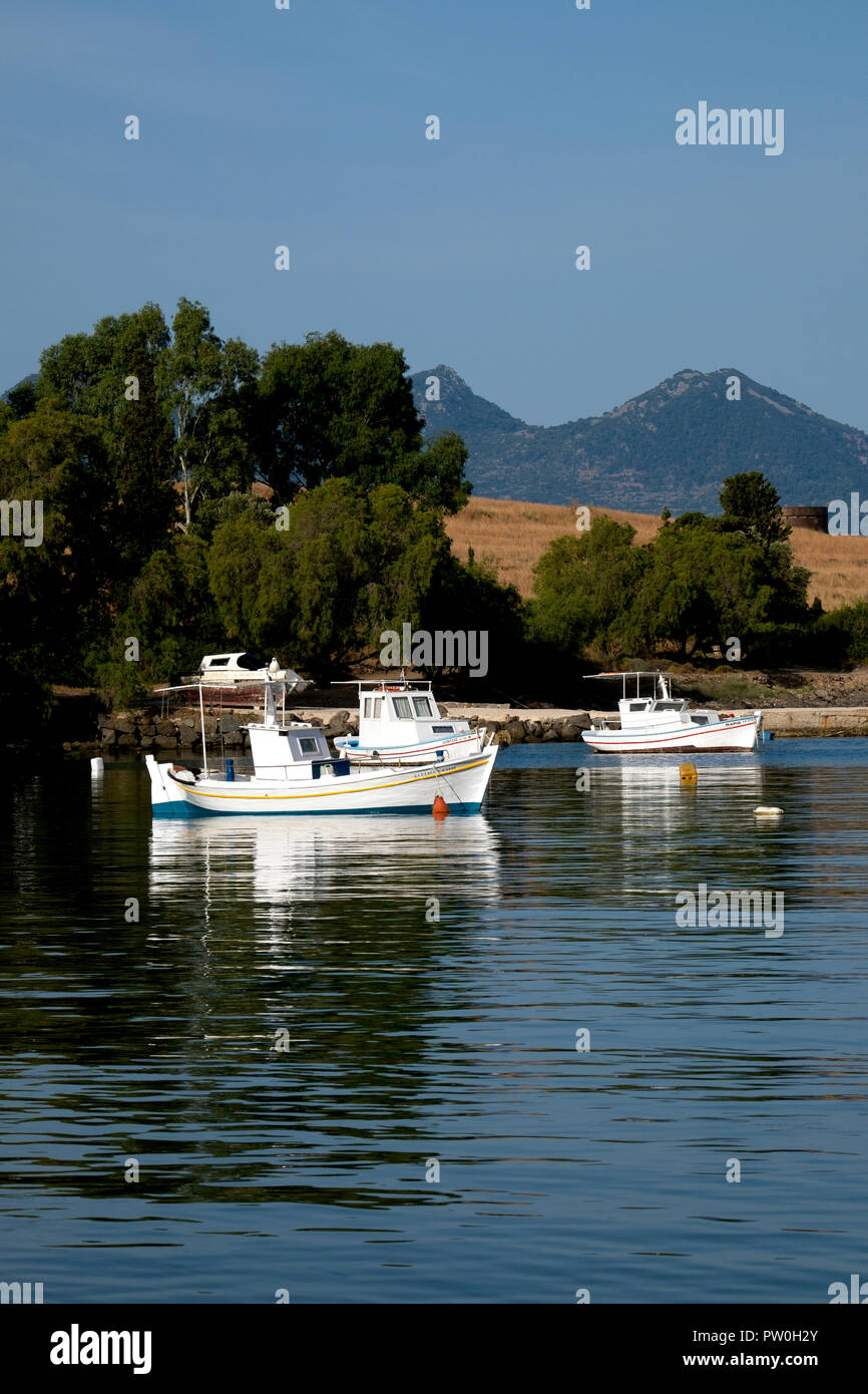 White fishing boats moored in the calm waters of Perdhika bay on the Argo-Saronic island of Aegina, Greece - Stock Image