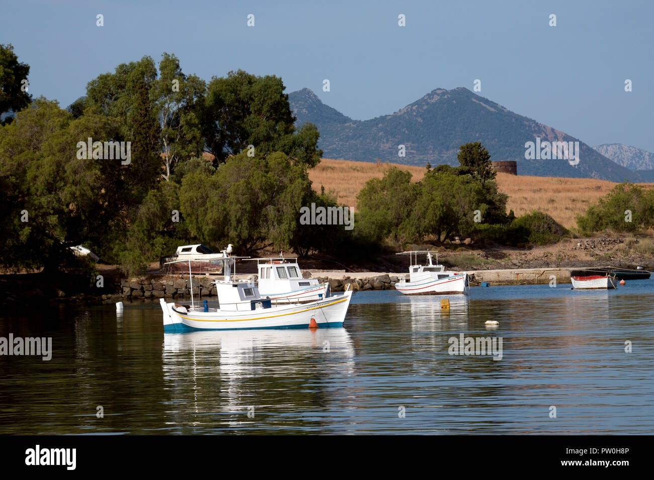 White fishing boats moored in the calm waters of Perdhika bay on the Argo-Saronic island of Aegina, Greece. - Stock Image