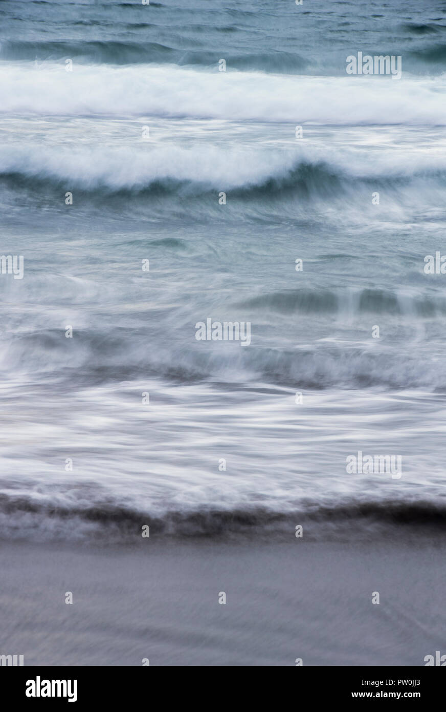 Long exposure of waves and the incoming tide splashing onto a sandy beach Stock Photo