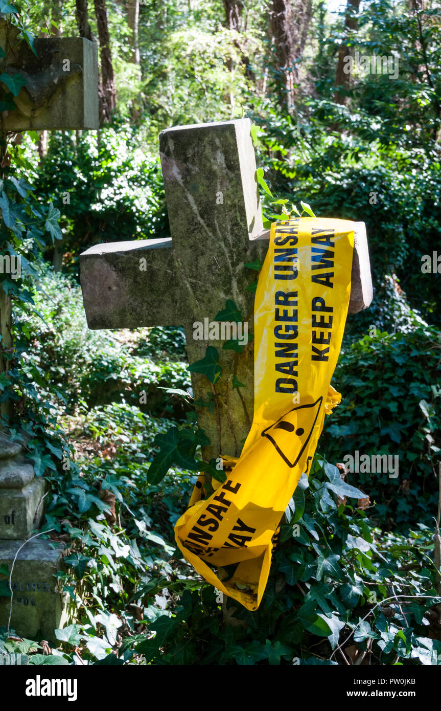A warning on an unsafe gravestone in Highgate Cemetery, London. - Stock Image