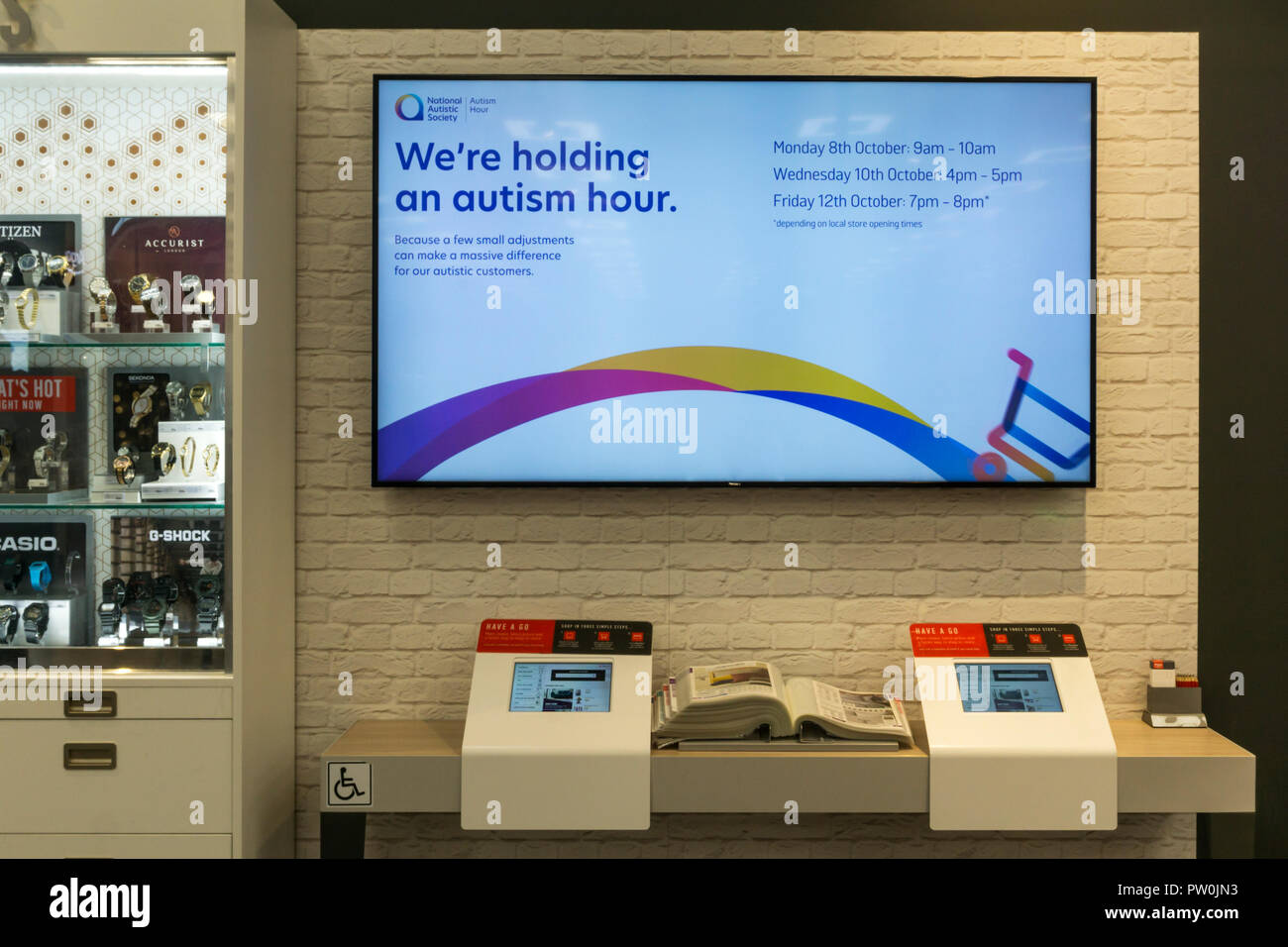 Wheelchair accessible terminals in Argos shop & screen announcing Autism Hour. - Stock Image