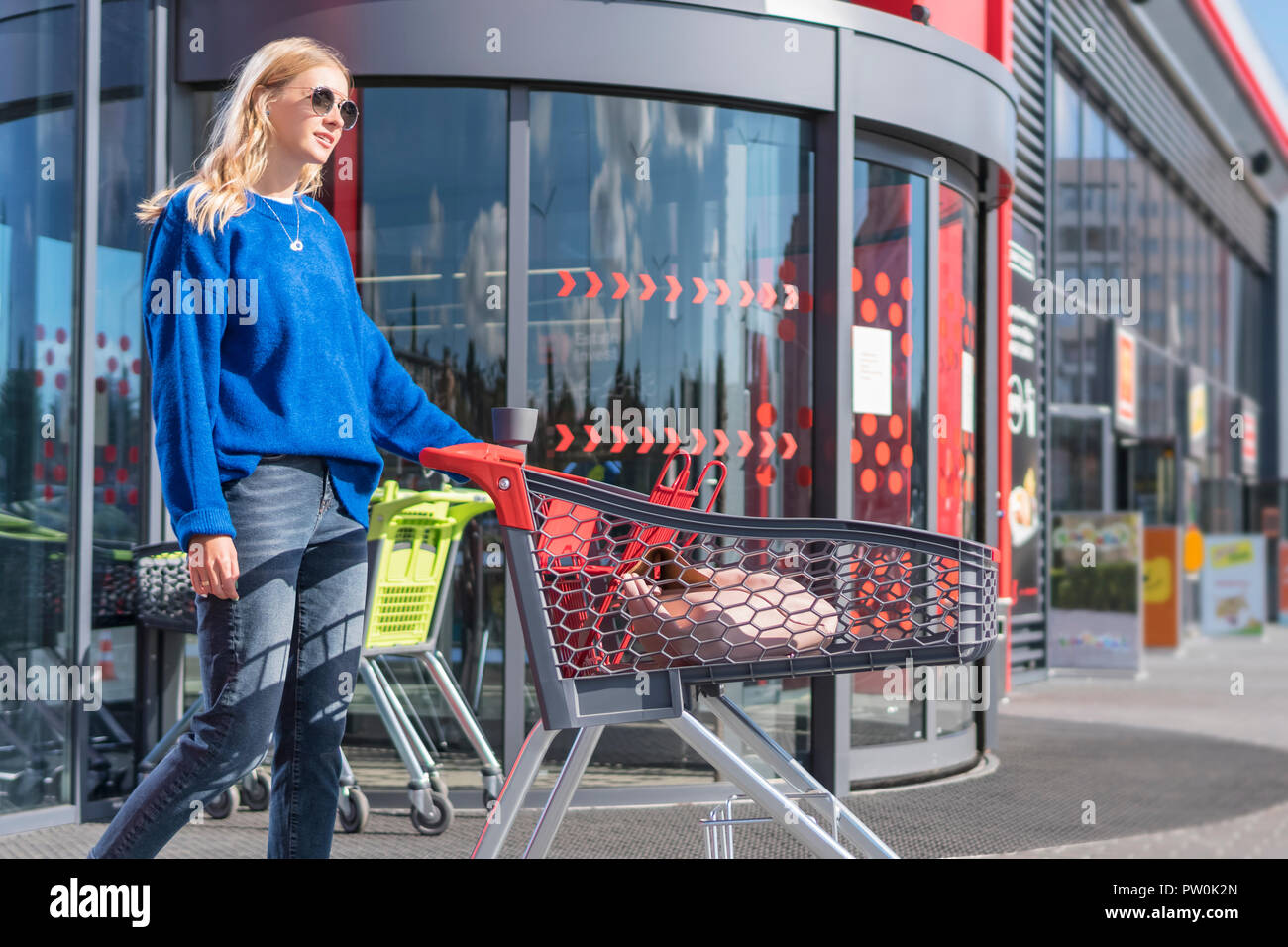 woman with trolley at the supermarket door - Stock Image