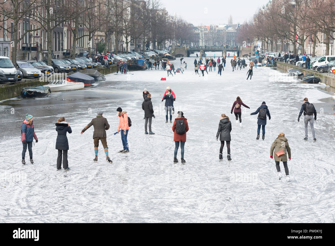 Ice on canal Keizersgracht, Amsterdam and ice skating people. A typical Dutch winter scene. Stock Photo