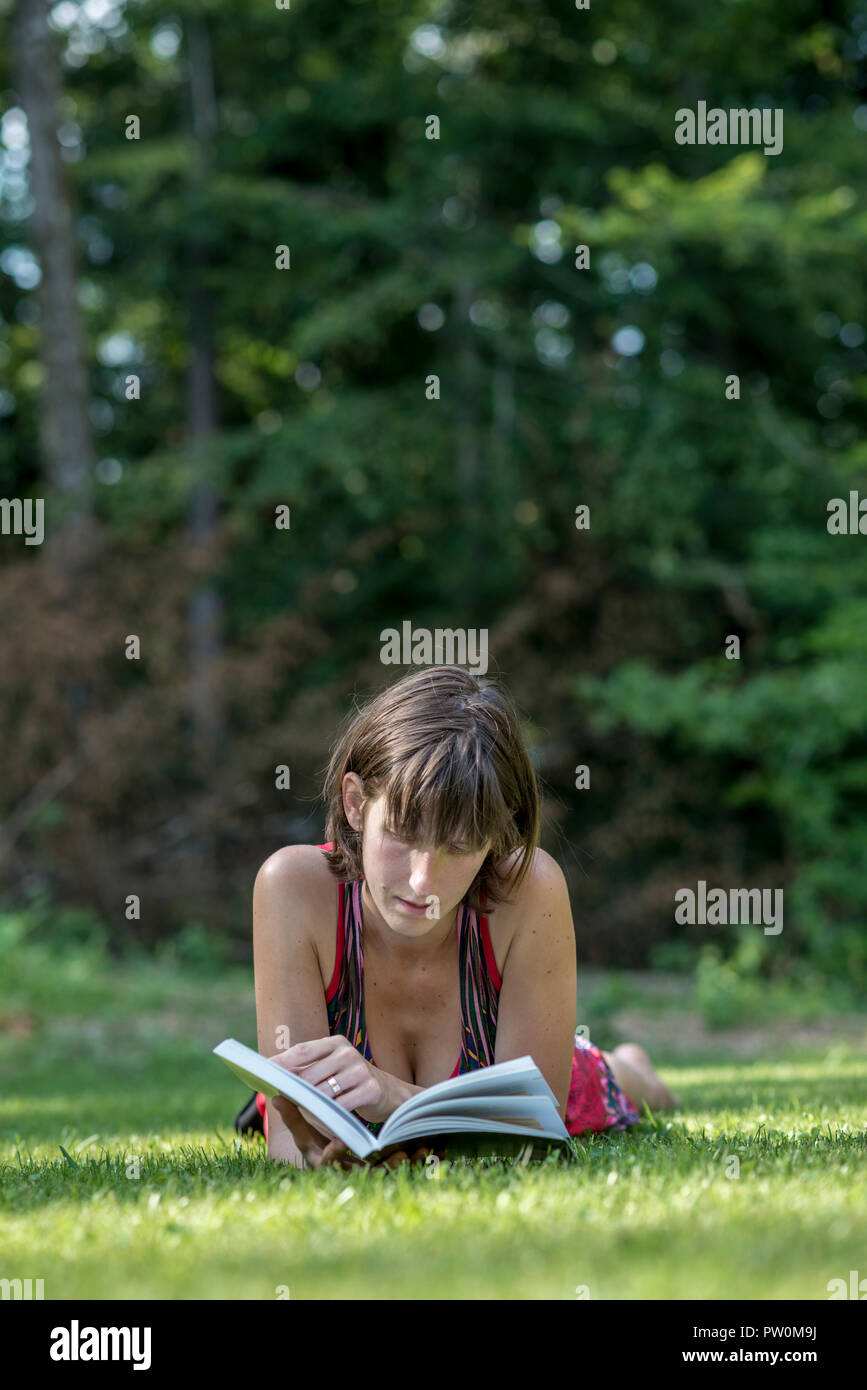 Single adult woman in sleeveless top laying down on grass reading a book with copy space over trees. - Stock Image