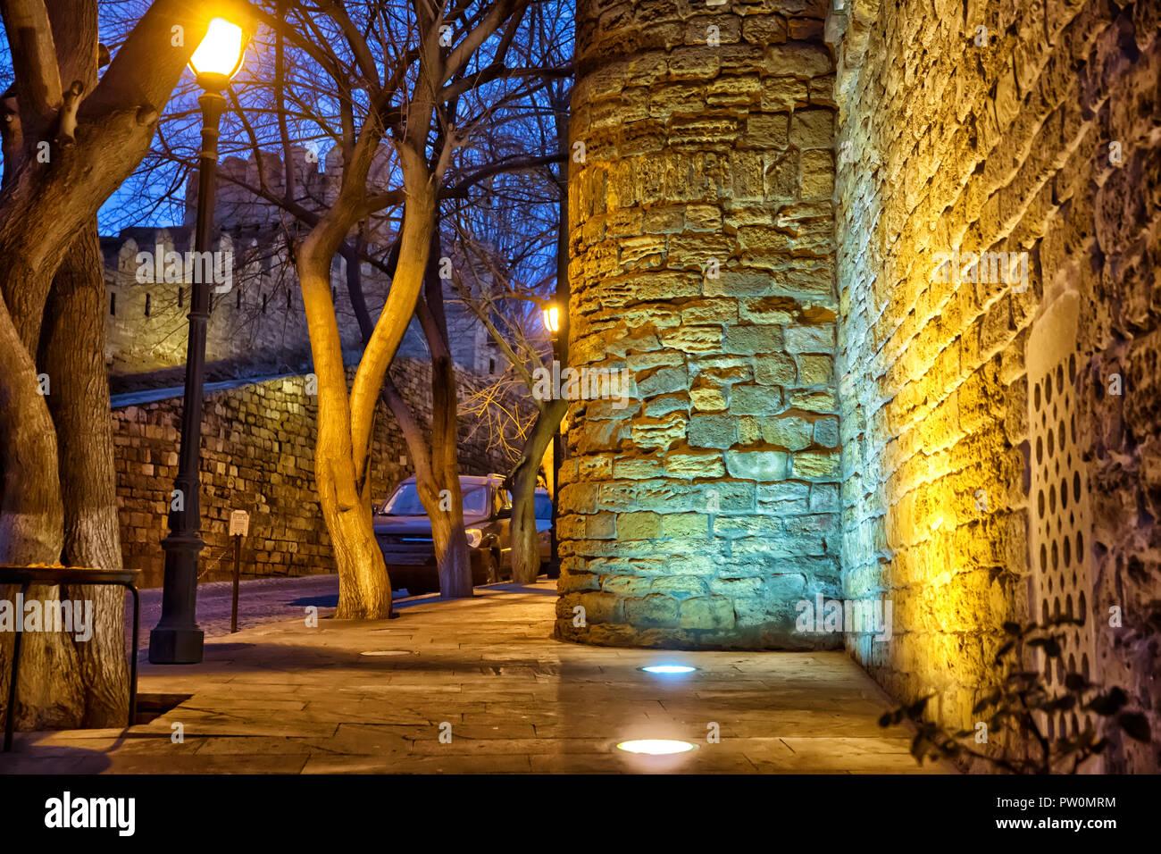 The fortress gates of the old city in the illumination . Icheri Sheher in night Baku. Azerbaijan . Gate of the old fortress, entrance to Baku old town - Stock Image