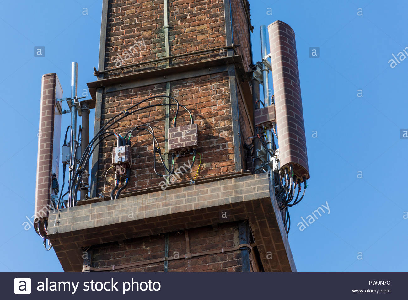 Mobile phone antennae on old industrial buildings on the Old Tannery Site in Holt, Wiltshire, previously connected with glove making in the area. - Stock Image