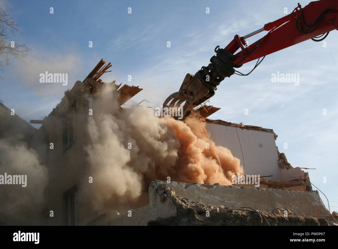 Tear down an old building with a excavator - Stock Image