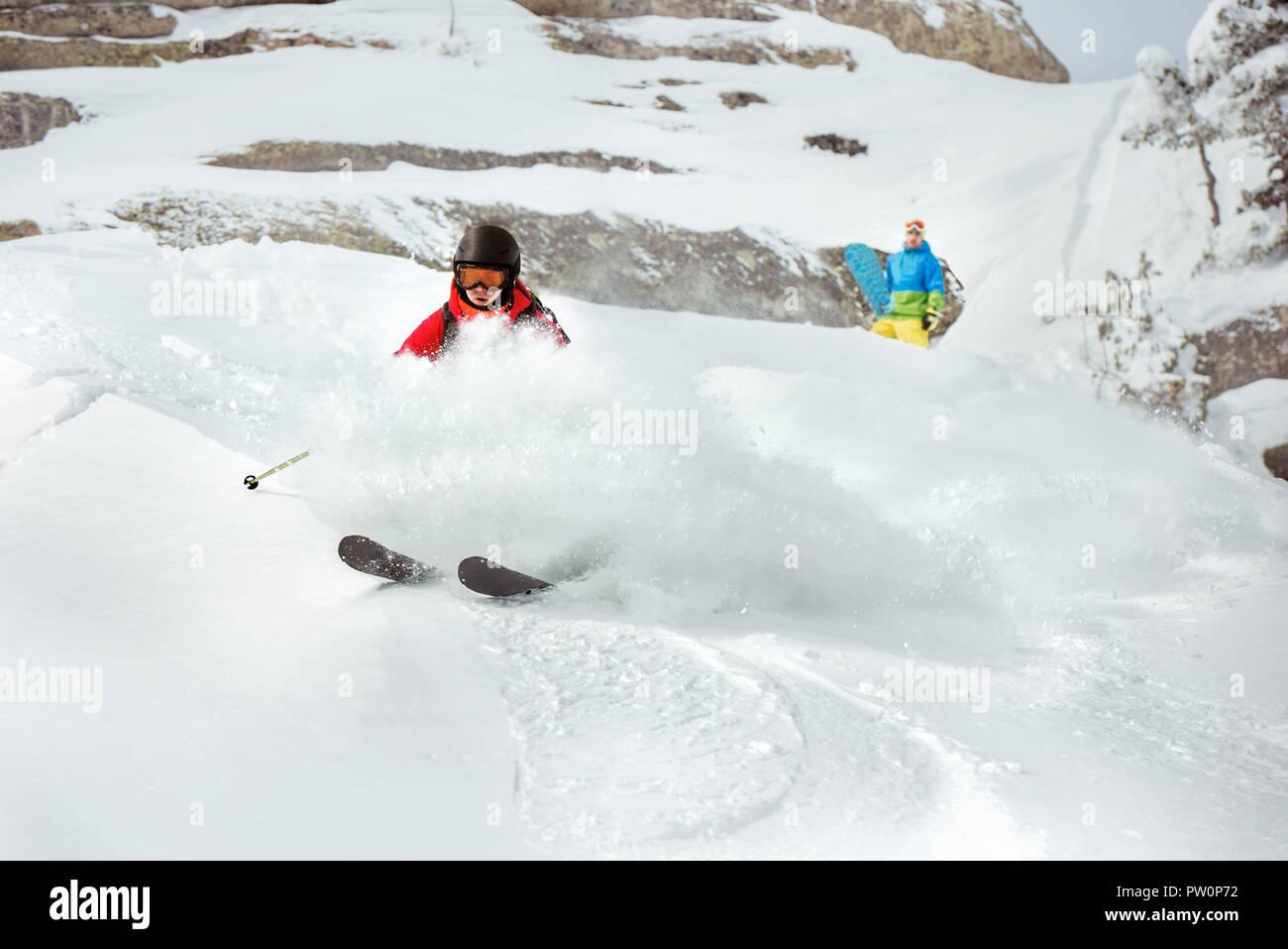 Skier freerides at offpiste slope against snowboarder and cliff. Ski resort concept - Stock Image