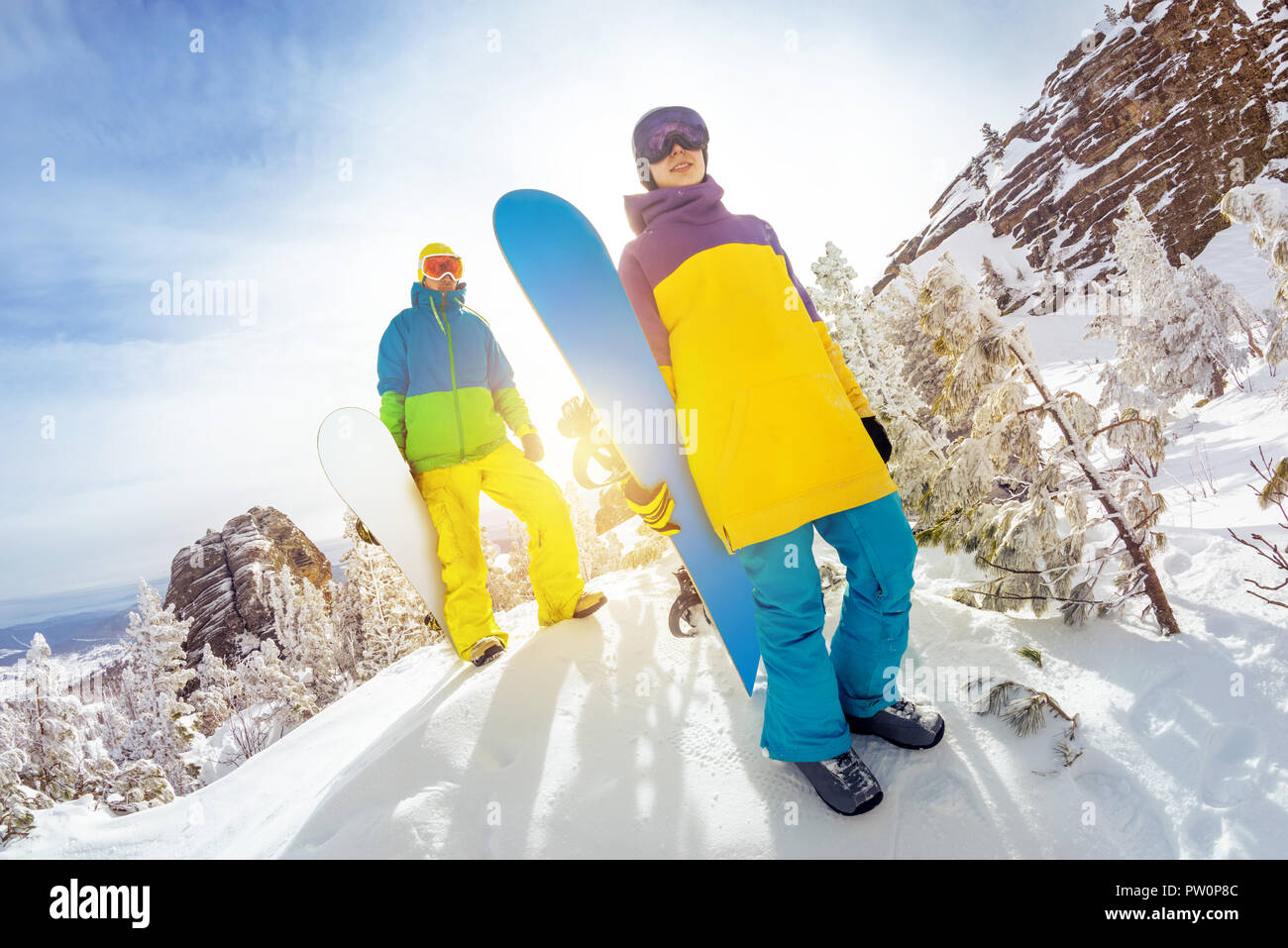 Two snowboarders male and female stands at offpiste ski slope with snowboards in hands - Stock Image