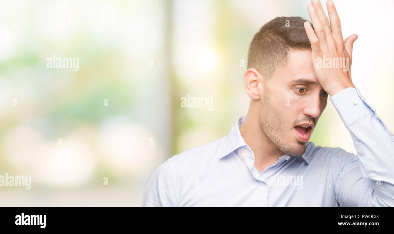 Handsome young businessman surprised with hand on head for mistake, remember error. Forgot, bad memory concept. - Stock Image
