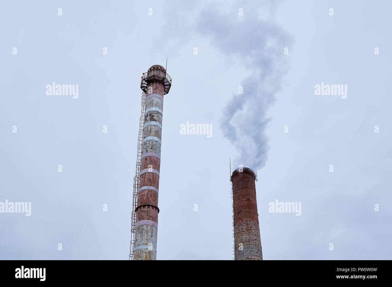 Smoking chimneys against the backdrop of an overcast sky. Industrial background. - Stock Image