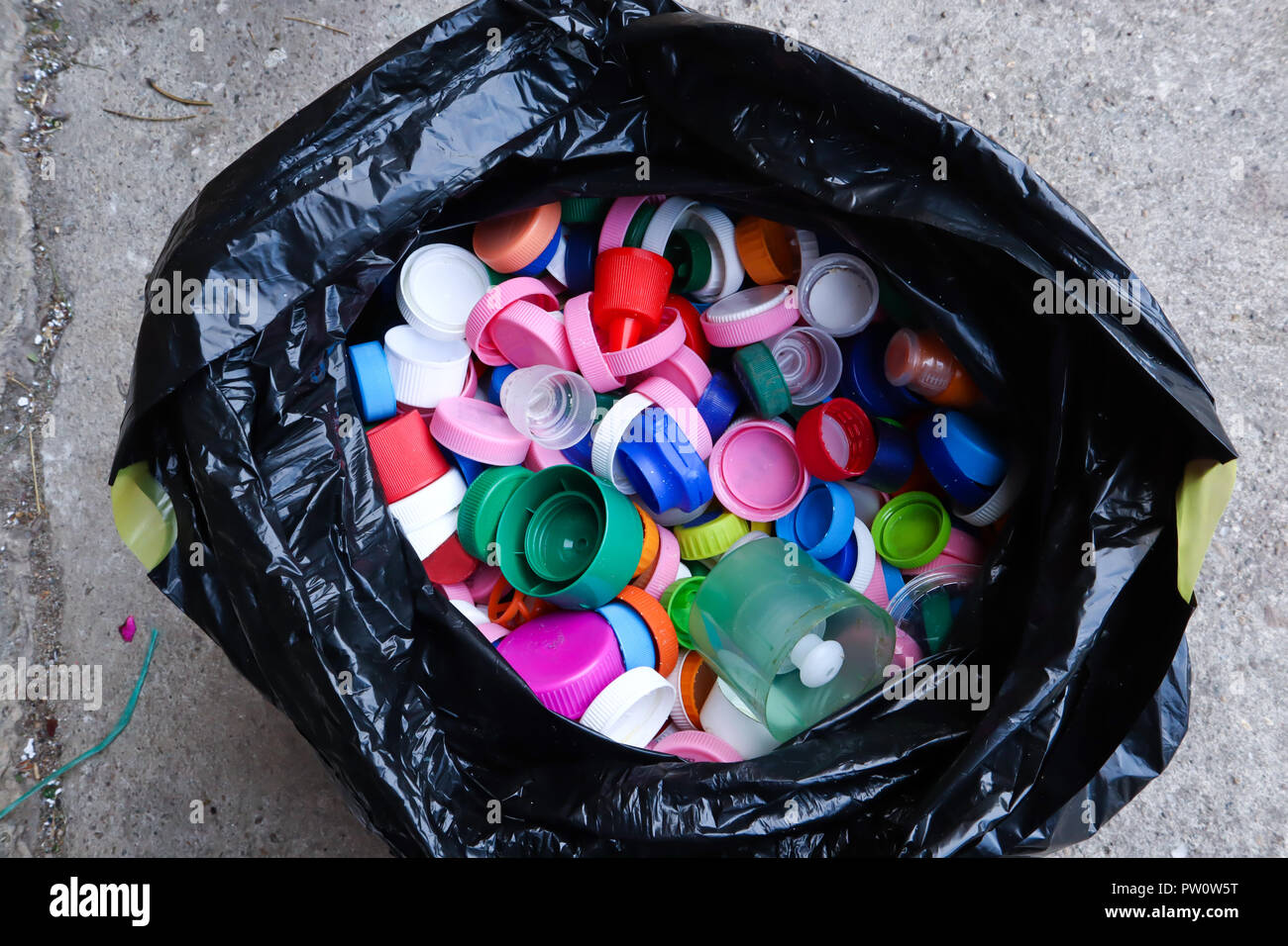 group of multicolored bottle caps in black plastic bag, ready for recycling top view - Stock Image