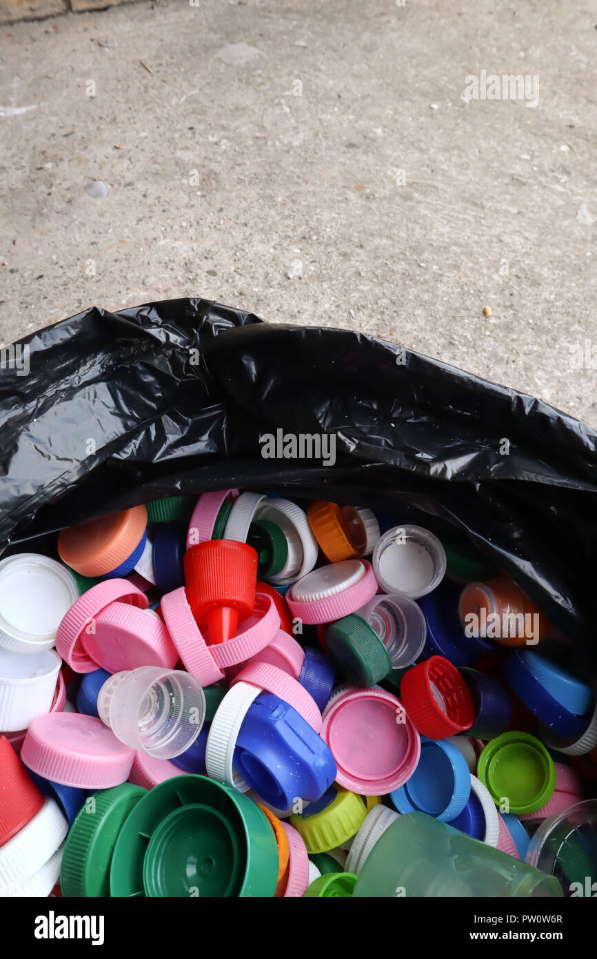 group of multicolored bottle caps in black plastic bag, ready for recycling top view, copy space - Stock Image