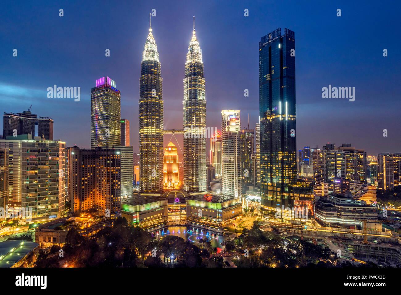 City skyline with Petronas Towers at night, Kuala Lumpur, Malaysia - Stock Image