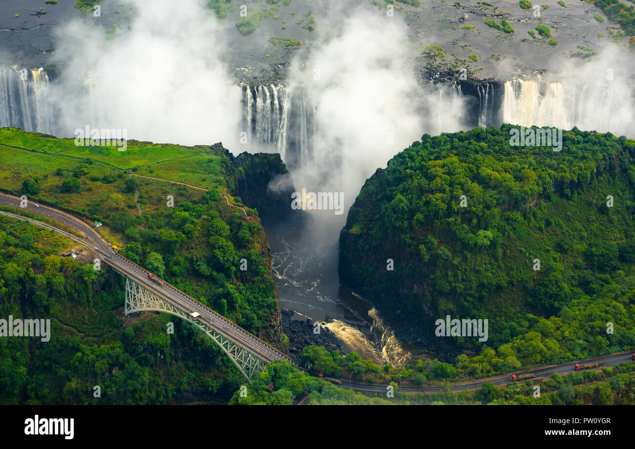 Victoria Falls in Zimbabwe and Zambia, Aerial helicopter photo, green forest around amazing majestic waterfalls of Africa. Livingston Bridge above the - Stock Image