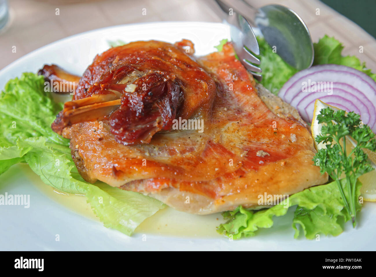 Lamb Shank Roast Served With Salad and Onion - Stock Image