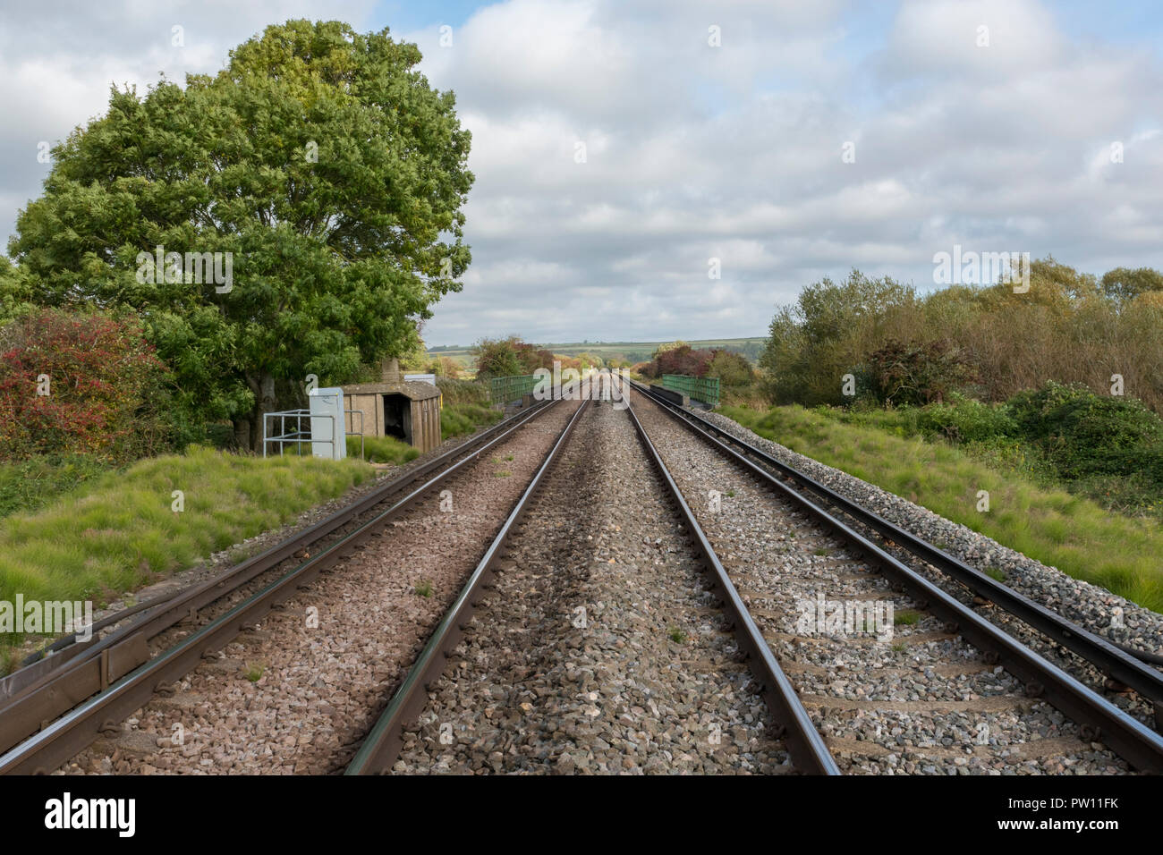 railway lines or rail train tracks tapering into the distance to a vanishing or disappearing point in the countryside. - Stock Image