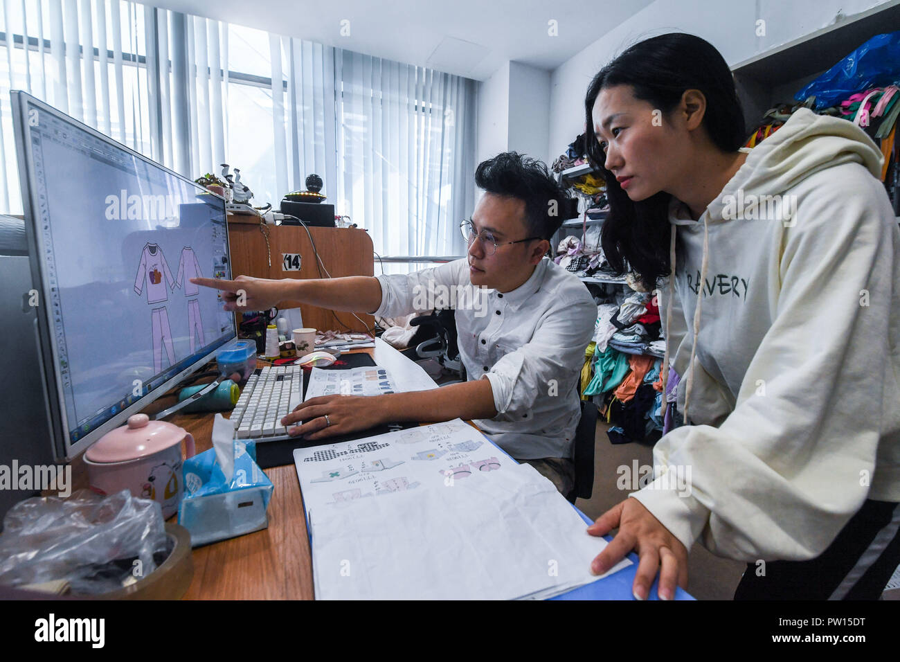 181011 Huzhou Oct 11 2018 Xinhua A Fashion Designer Discusses Children S Clothing Designs With A Colleague At A Children S Clothing Design Center In Zhili Town Of Huzhou East China S Zhejiang