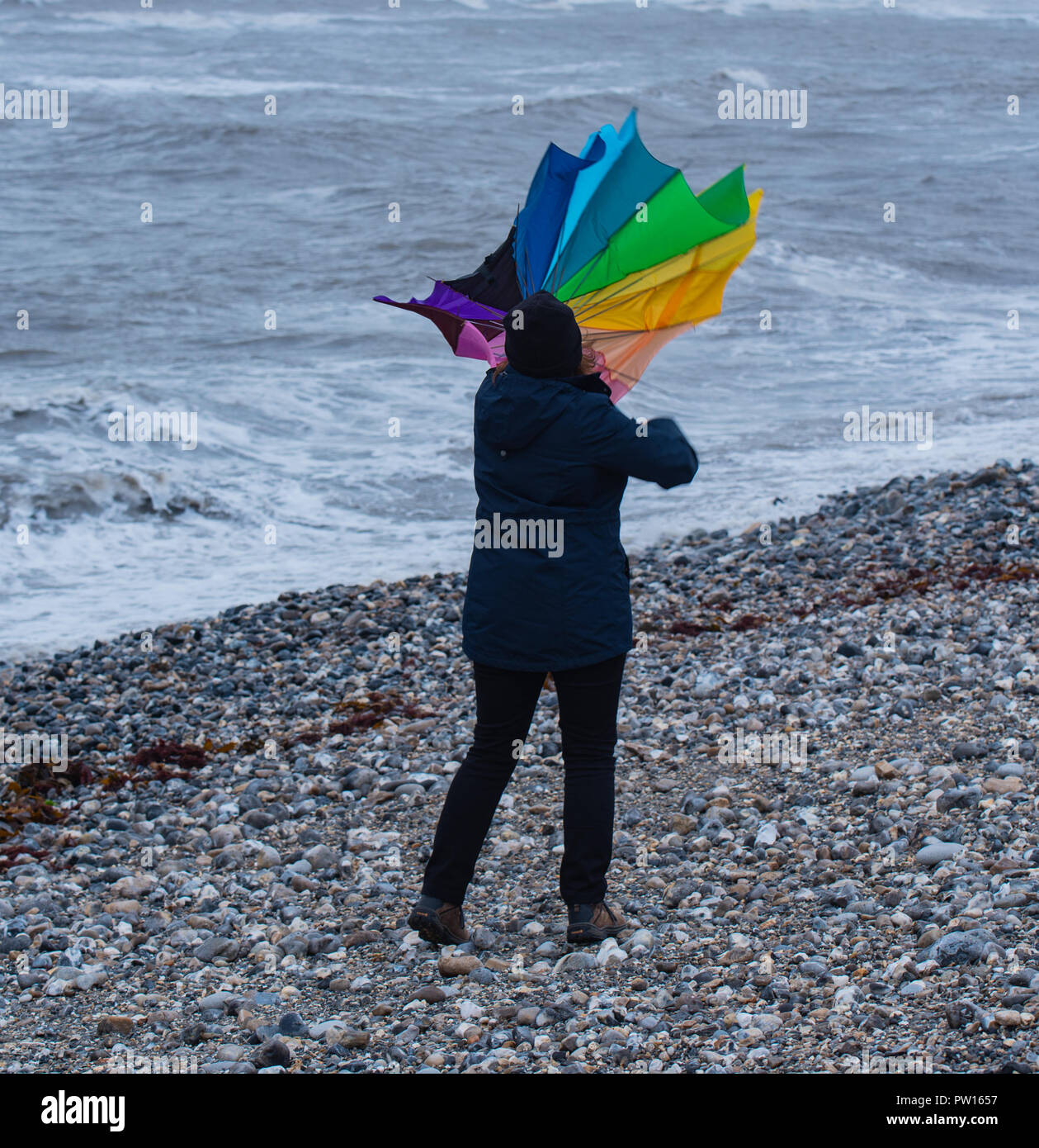 Lyme Regis, Dorset, UK. 11th October 2018.  UK Weather:   A woman battles with an umbrella on the beach as gusty high winds and outbreaks of rain hit the coastal resort of Lyme Regis ahead of Storm Callum.  Credit: Celia McMahon/Alamy Live News - Stock Image