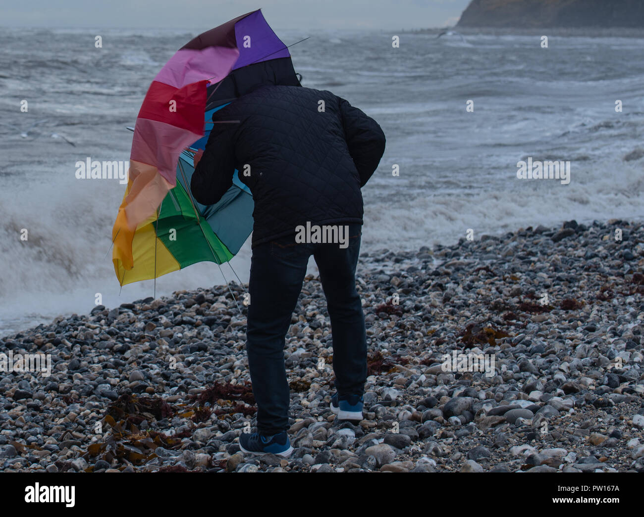 Lyme Regis, Dorset, UK. 11th October 2018.  UK Weather:   A man battles with an umbrella on the beach as gusty high winds and outbreaks of rain hit the coastal resort of Lyme Regis ahead of Storm Callum.  Credit: Celia McMahon/Alamy Live News - Stock Image