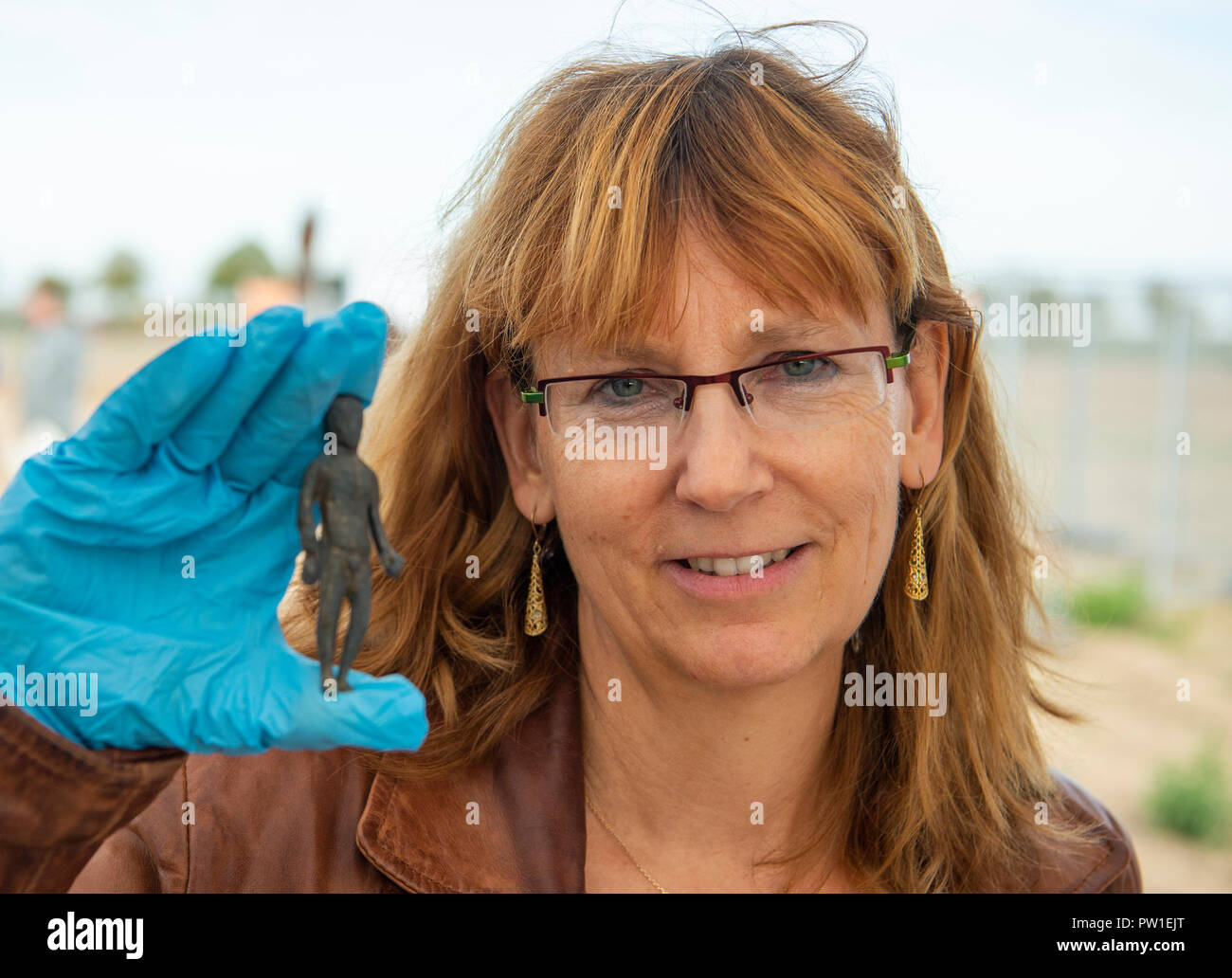 12 October 2018, North Rhine-Westphalia, Moenchengladbach: Kerstin Kraus, archaeologist at the Landschaftsverband Rheinland - Amt für Bodendenkmalpflege ('Agricultural Association Rhineland - Office for Archaeological Site Care'), holding a figure from an archaeological find. Two finders have discovered a large amount of coins from the 4th/5th century with detectors. Photo: Christophe Gateau/dpa Stock Photo