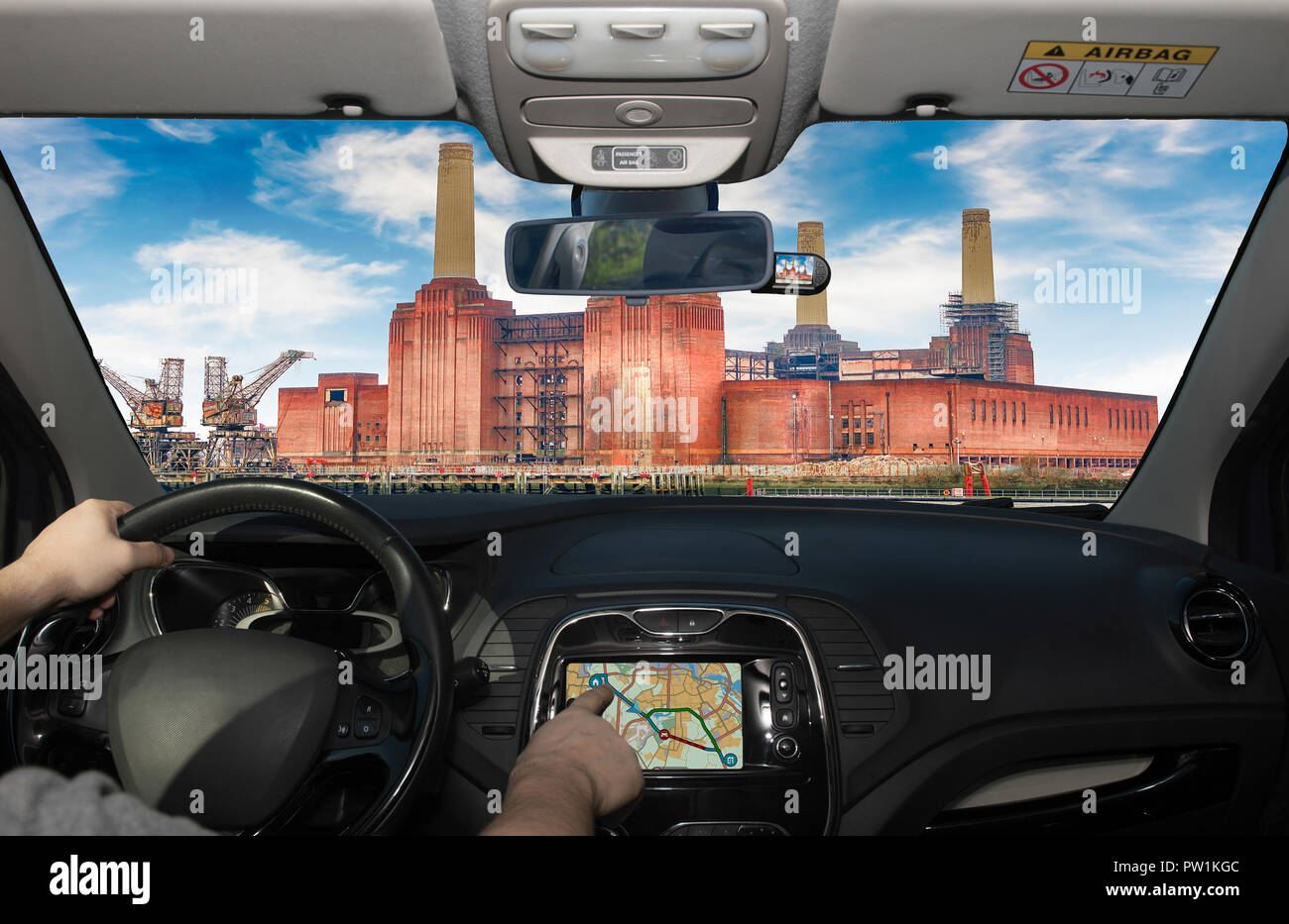 Driving a car while using the touch screen of a GPS navigation system towards Battersea Power Station, London, UK - Stock Image