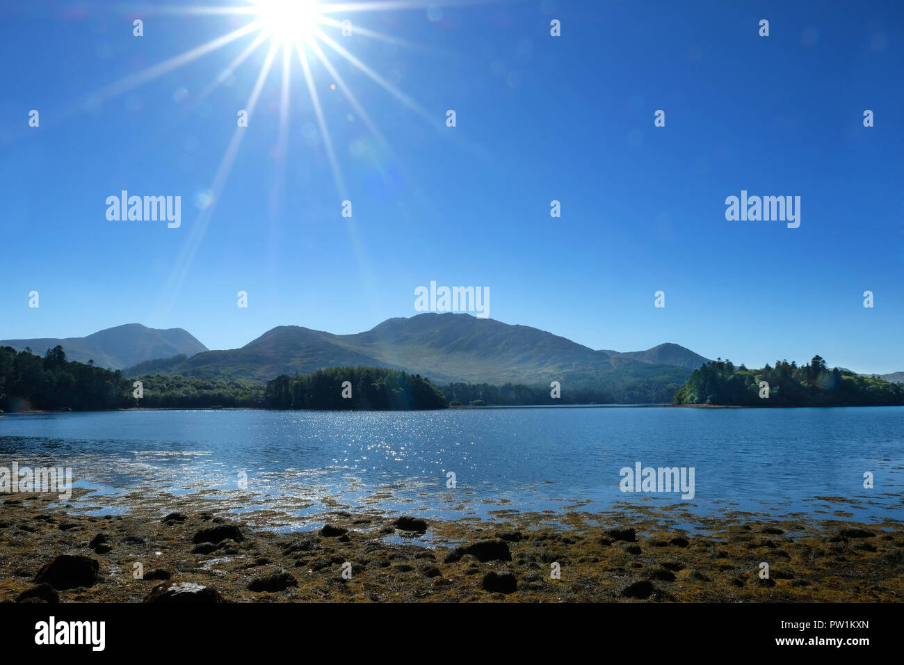 Kenmare River on the County Kerry coast, Ireland, with plenty of lens flare - John Gollop - Stock Image