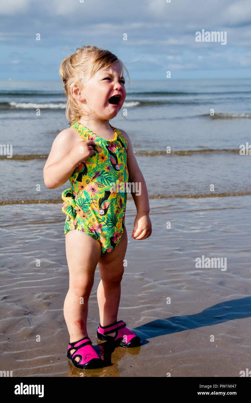 A young toddler girl having a tanturm on the beach in her swimming costume and beach shoes - Stock Image
