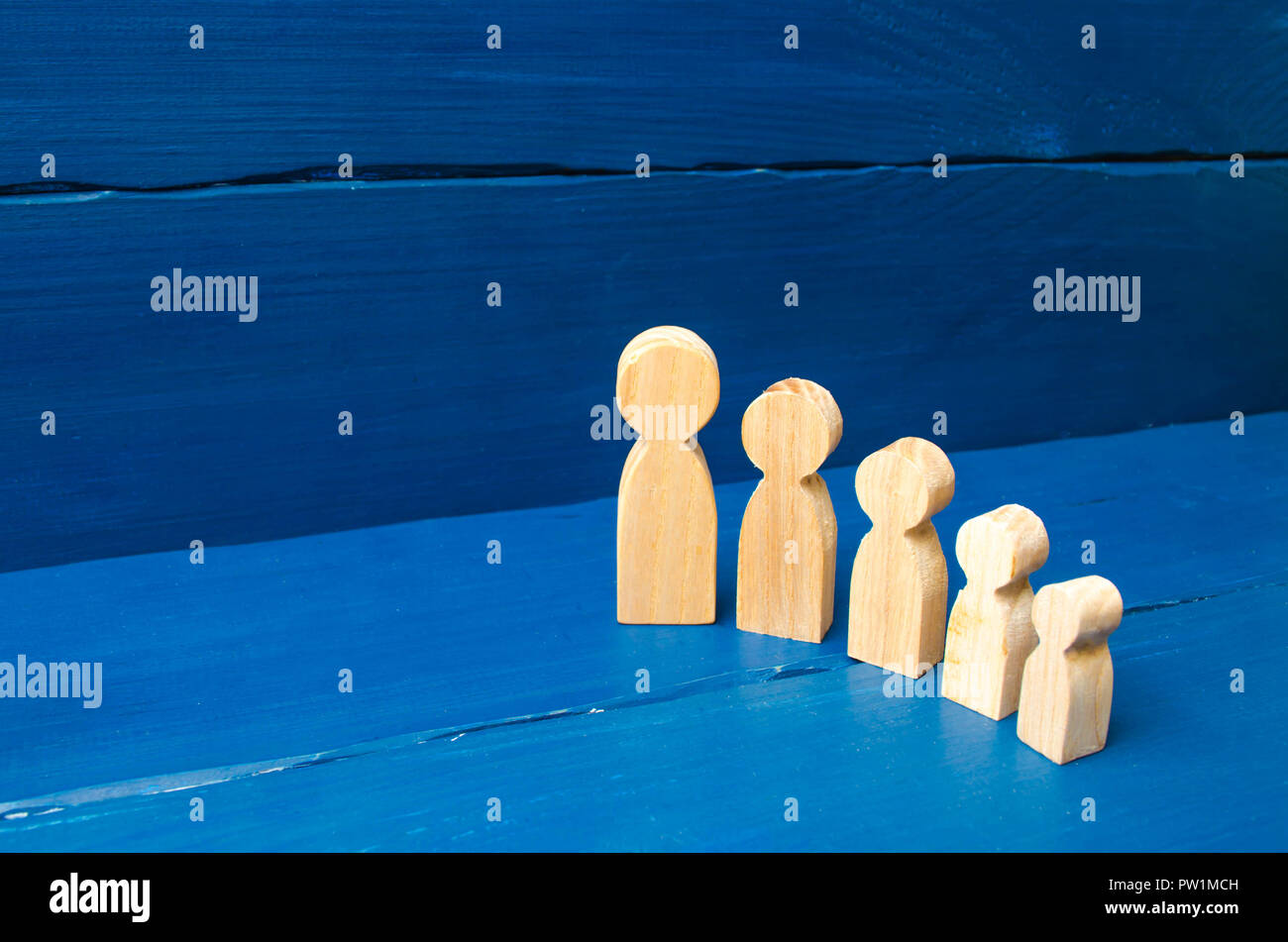 The concept of self-development, growth of personality and professionalism. Children and parents, family. The cycle of human growth. Wooden figures of - Stock Image