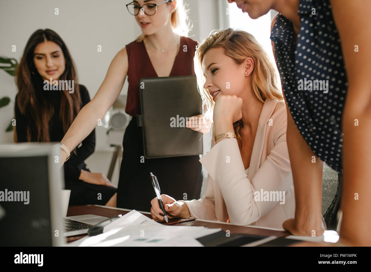 Group of young businesswomen in casuals looking at laptop and discussing work. Multi-ethnic female coworkers working together in office. Stock Photo