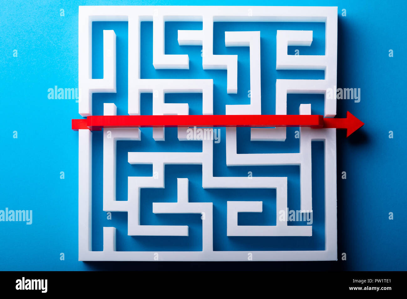 Elevated View Of Red Arrow Crossing Over White Maze On Blue Background - Stock Image