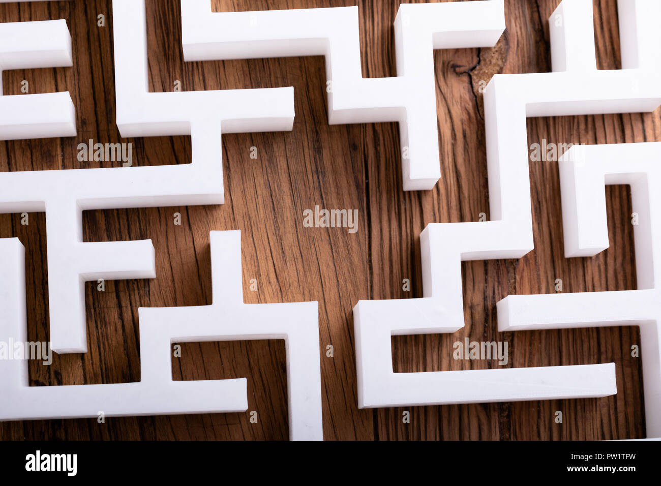 Overhead View Of Abstract White Maze On Wooden Background - Stock Image