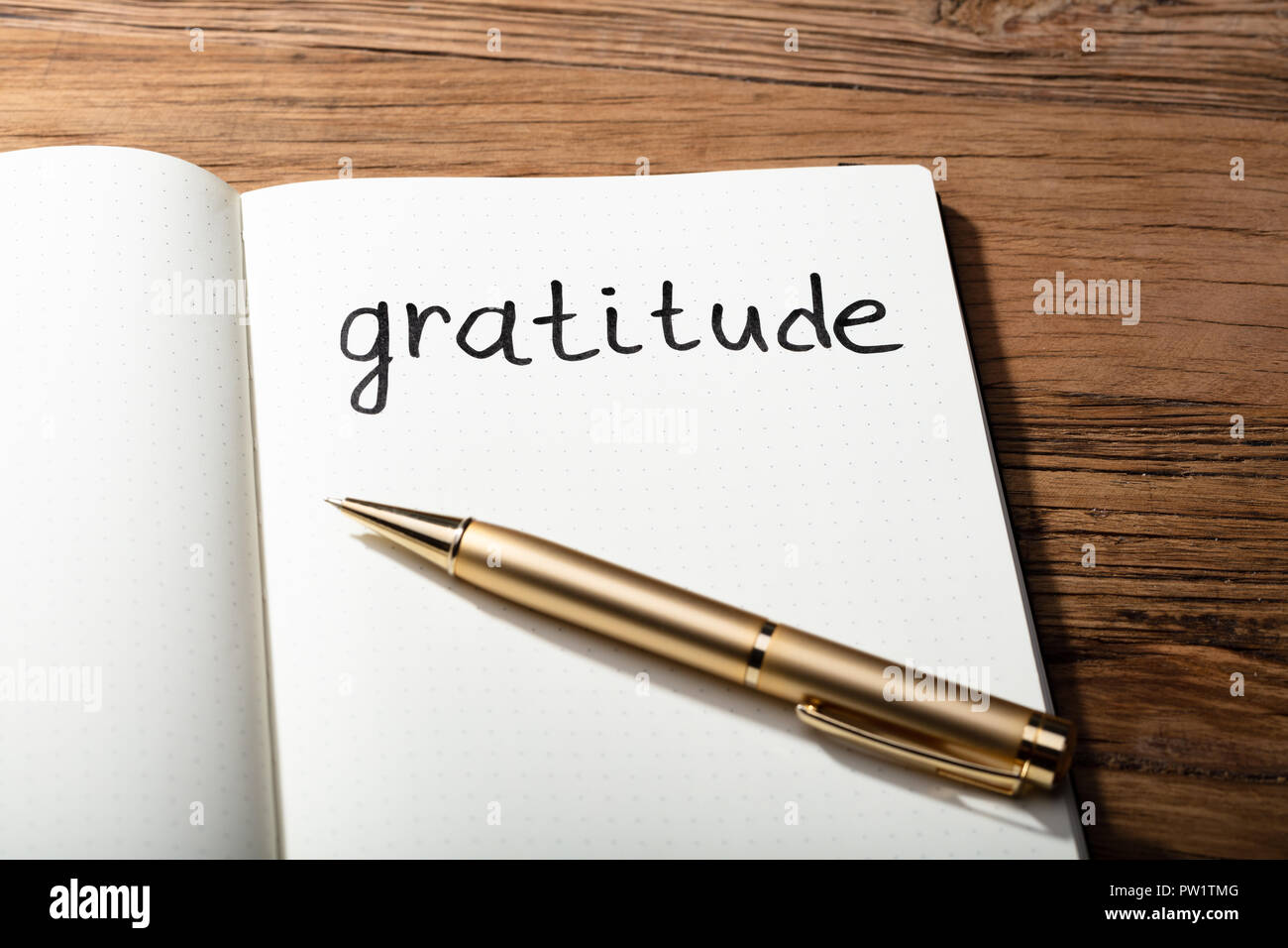 Close-up Of Gratitude Word With Pen On Notebook Over Wooden Desk - Stock Image