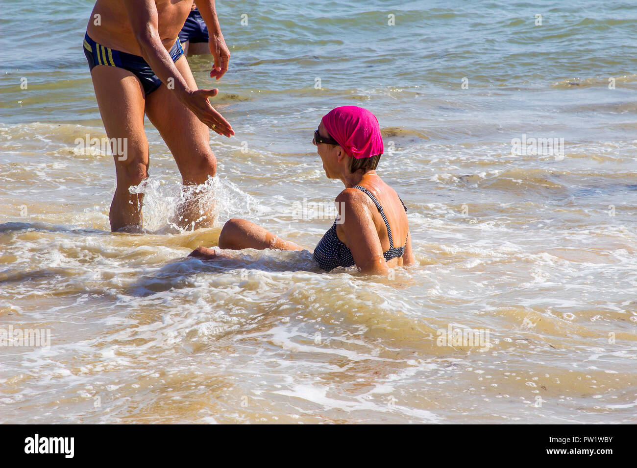 29 september 2018 A man with outstretched hand to help a lady who has fallen been swept of her feet by the breaking waves on a beach in Albuferia Port Stock Photo