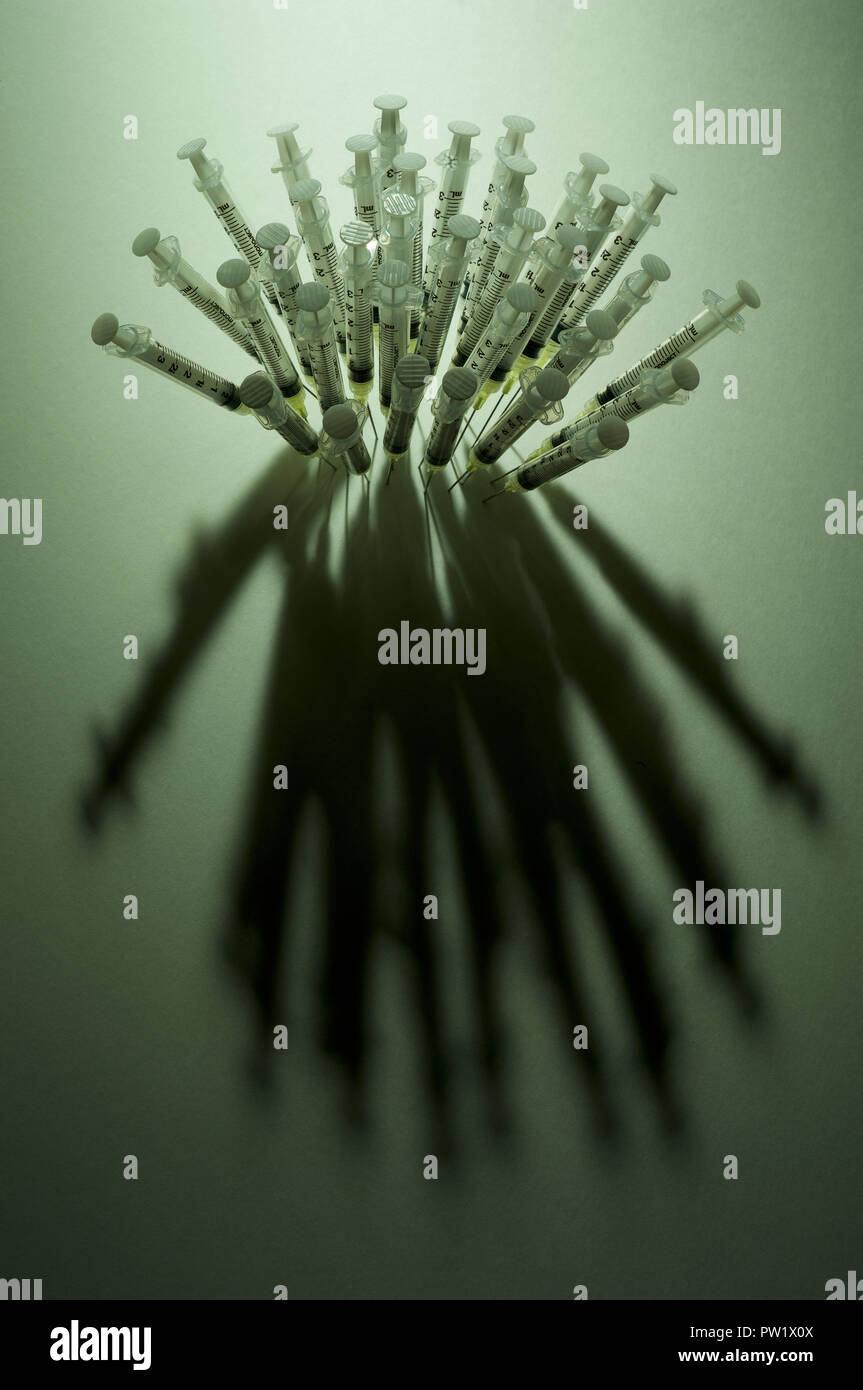 Concept A group of Syringes Needles close Together Piercing a Surface, Opioids Crisis, American Addiction, Drug Abuse, Opioids Epidemic - Stock Image