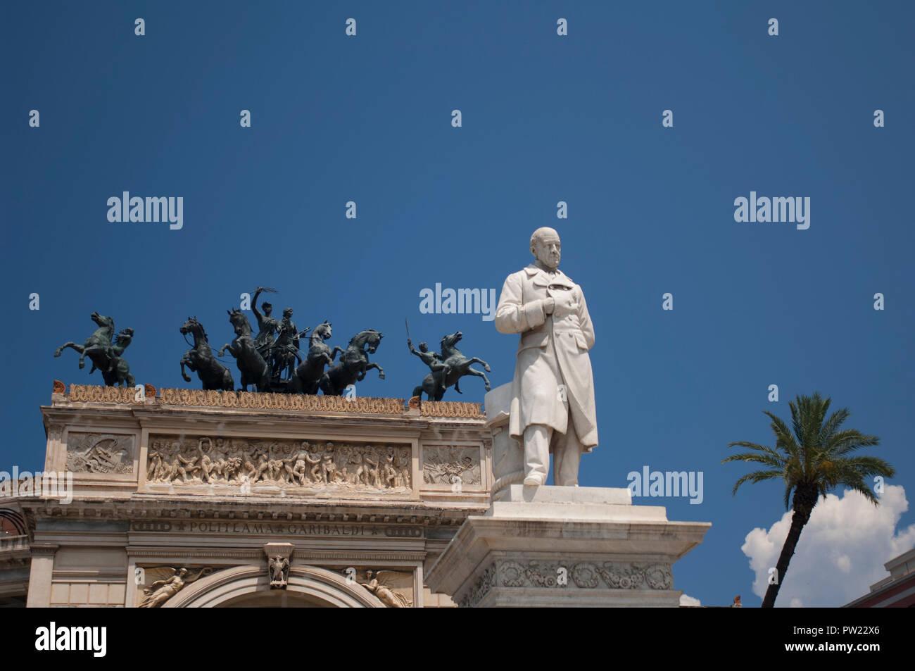 Bronze horses of a quadriga on top of the portico of the Teatro Politeama Garibaldi, with a statue of Ruggero Settimo in the foreground Stock Photo