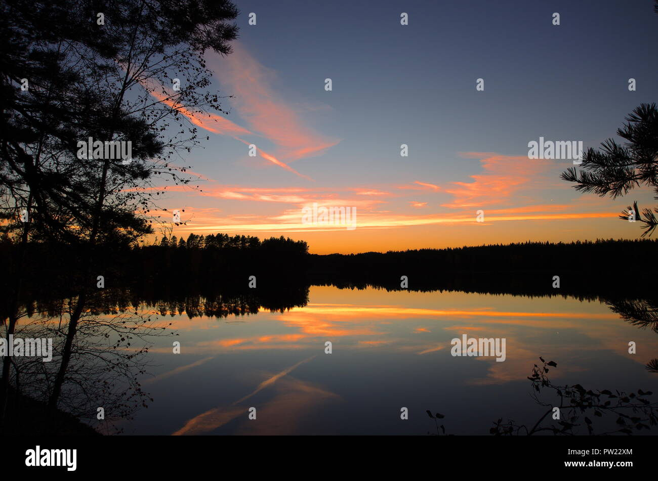 Beautiful and colourful autumn sunset over a lake surrounded by forests in Dalarna,Sweden. - Stock Image