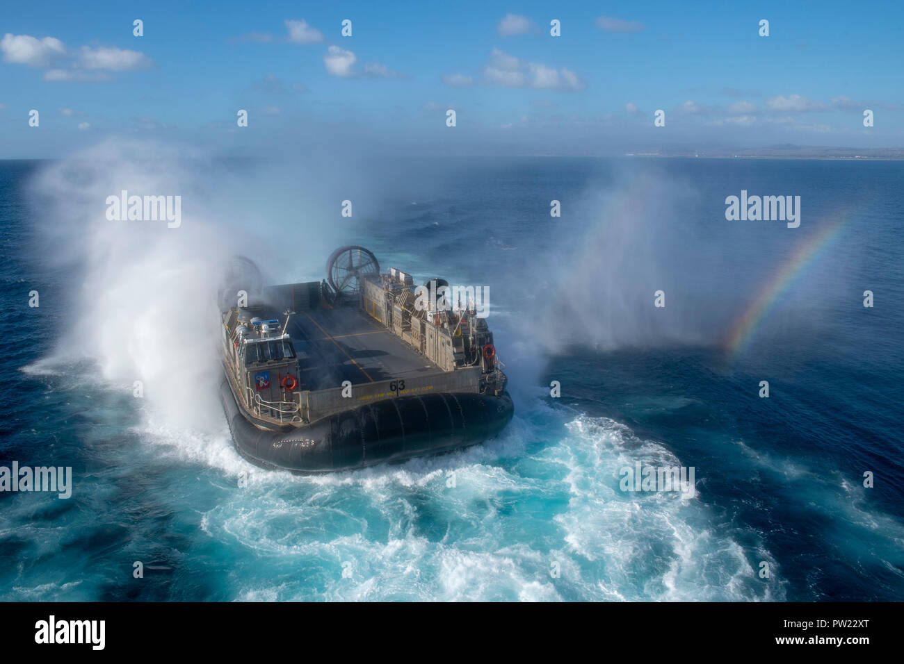 181010-N-DC385-1117 PACIFIC OCEAN (Oct. 10, 2018) Landing craft air cushion (LCAC) 63, assigned to Assault Craft Unit (ACU) 5, approaches the well deck of the amphibious assault ship USS Bonhomme Richard (LHD 6). Bonhomme Richard is operating in the U.S. 3rd Fleet area of operations. (U.S. Navy photo by Mass Communication Specialist 3rd Class Cosmo Walrath) - Stock Image